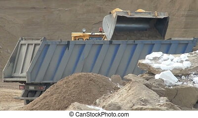 Close-up of loading sand in container at huge sandpit
