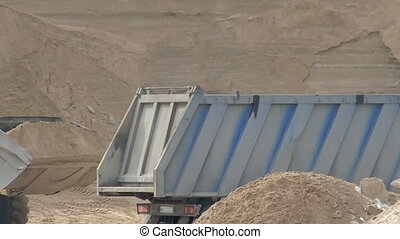 Close-up of wheel loader loads sand in container - View of...