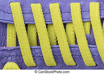 Closeup of colorful shoe laces in yellow on purple leather