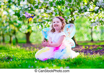 Little girl in fairy costume feeding a bird