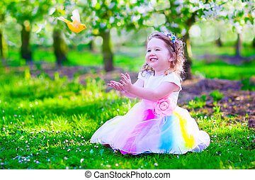 Little girl in fairy costume feeding a bird - Child playing...