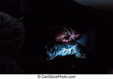Teenager boy on smart phone in his room late at night.