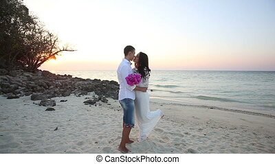 bride and groom hug at sand beach at sunrise - brunette...