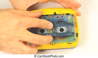 Inserting cassette in tape recorder - A static camera view...