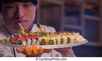 Smiling Asian chef in white uniform standing in kitchen of sushi bar turning plate with rolls