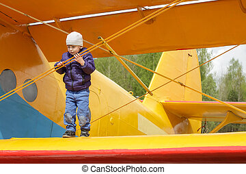 Child on the wing of an airplane - Two years old kid...