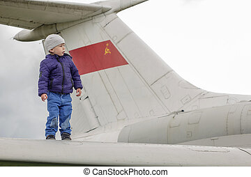 Child on the wing of a jet plane - Two years old kid...