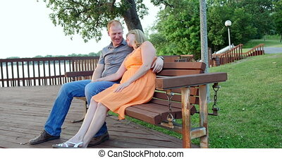 Young couple sitting together - Young couple, in love,...