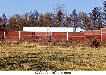 noise barrier and trucks - a noise barrier protects against...