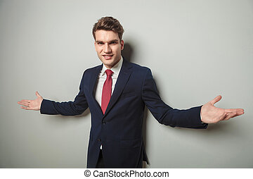 Happy young business man welcoming you with his arm open