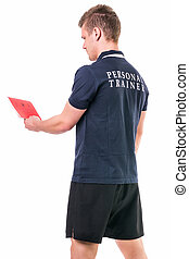 Handsome young personal trainer with clipboard, standing