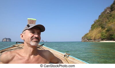 old man drifts in longtail boat to island beach - old trunk...