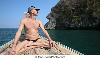 old man sits in longtail boat as yogi drifting to island...