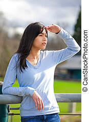 Young teen girl standing, leaning against railing at park...