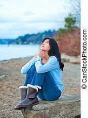 Teen girl sitting on boulder along lake shore praying