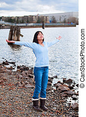 Young teen girl with arms lifted and outstretched, praising God on rocky shore by lake