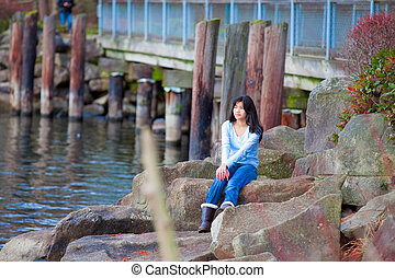 Young teen girl sitting on large boulders along lake shore, looking out over water