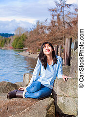 Happy young teen girl face upturned, smiling, while sitting outdoors on rocks along lake shore