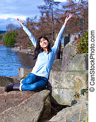 Young teen girl arms raised while sitting on large rock along lake shore, happy