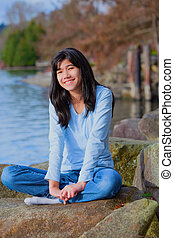 Young teen girl relaxing on large boulder along lake shore, smiling