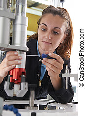Apprentice Female Engineer Working On Machine In Factory