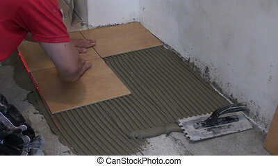 man tile bond floor - man hand placing bond ceramic floor...