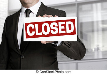 Businessman holding closed sign to viewer.