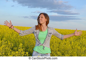 Beautiful girl posing in a field of yellow flowers