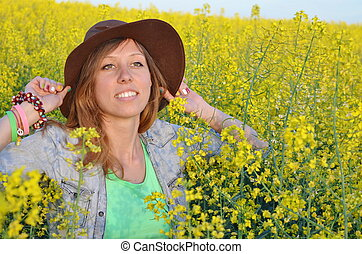 Beautiful girl posing in a field of yellow flowers -...