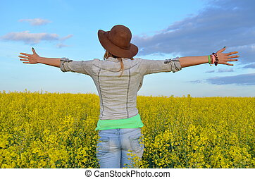 Girl posing in a field of yellow flowers - Girl posing with...