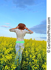 Girl looking at field of yellow flowers - Girl posing with a...