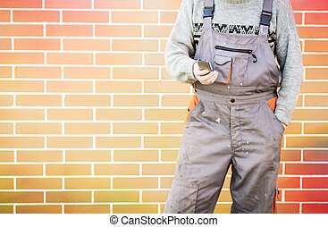 Anonymous handyman with mobile phone, 24/7 help concept