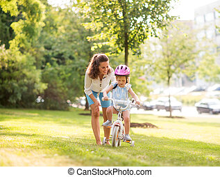 Mother teaching her daughter how to ride a bicycle in a park...