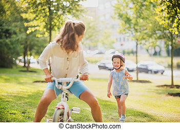 Mother playfully riding a blonde girls bike in a sunny park...