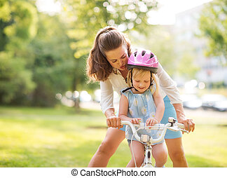 Mother shows daughter how to ride a bike holding handlebars...