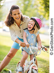 Laughing mother and daughter learning how to ride a bike -...