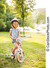 Girl in pink helmet sitting on her bike in a sunny city park...