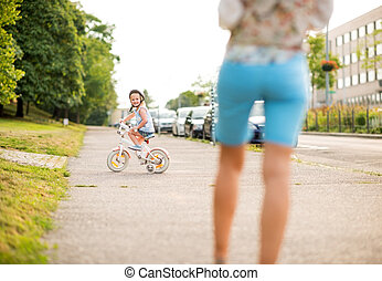Smiling girl rides her bike on city sidewalk as mother...
