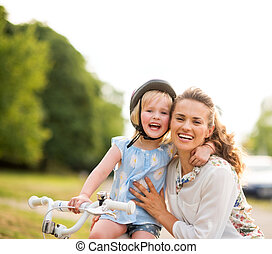 Proud girl on a bicycle hugging her mother in a city park -...