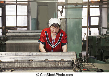 Woman working on the machine at factory