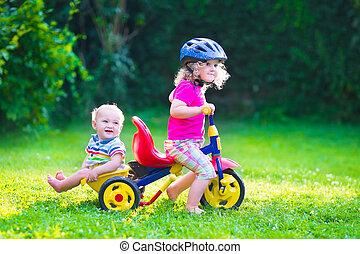 Two kids on a bike - Children riding a bike. Kids enjoying a...