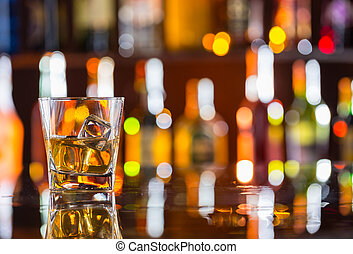 Whiskey drink on bar counter with blur botles on backgorund