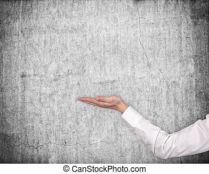hand holding invisible object on gray wall background