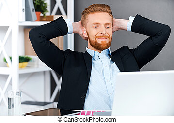 Having some rest for productive work. Cheerful bearded businessman holding head in hands while sitting at his working place