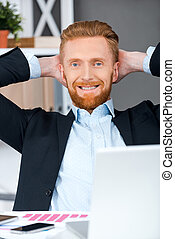 Rest for progress. Cheerful bearded businessman holding head in hands while sitting at his working place