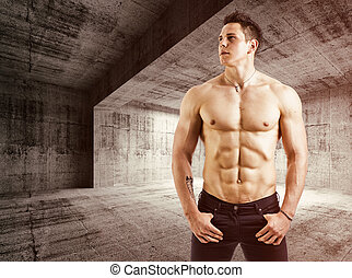 Muscular shirtless young man with jeans, indoors in empty...