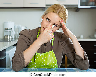Sad woman sitting at kitchen - Unhappy lonely blonde girl...