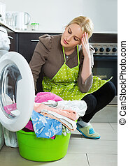 Tired woman doing laundry - Tired blonde woman doing laundry...