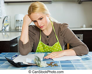 Serious woman calculating family budget - Serious woman...
