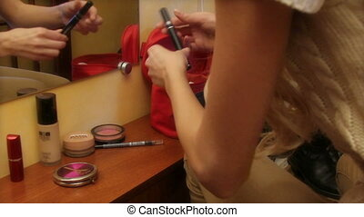 Beautiful young girl applying cosmetic in front of mirror